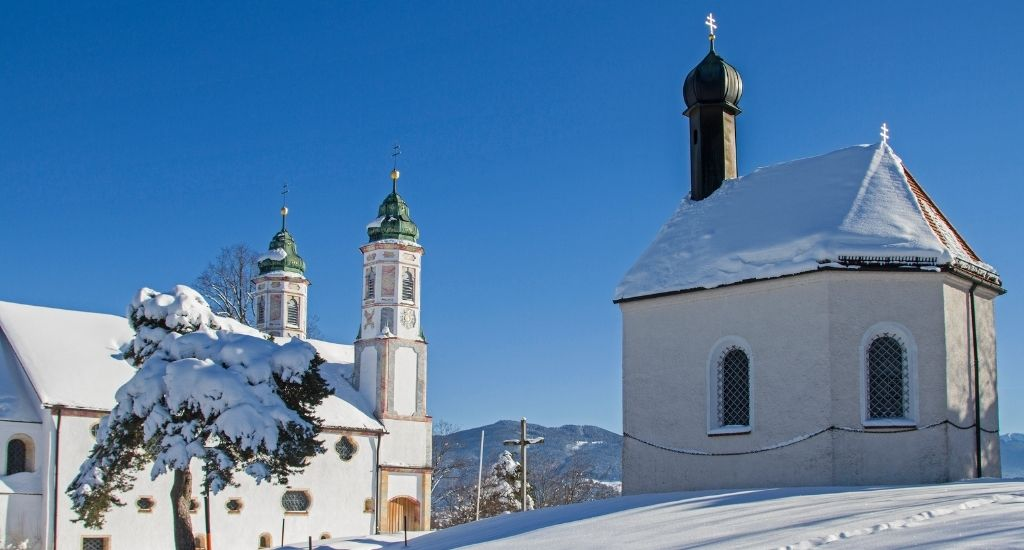 small chapel on the right and larger church on the left, covered with a thick layer of snow on a sunny winter day