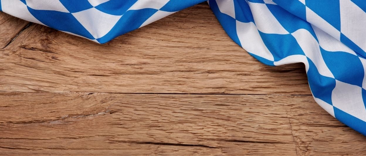 Wood table with blue and white bavarian flag draped over top right corner