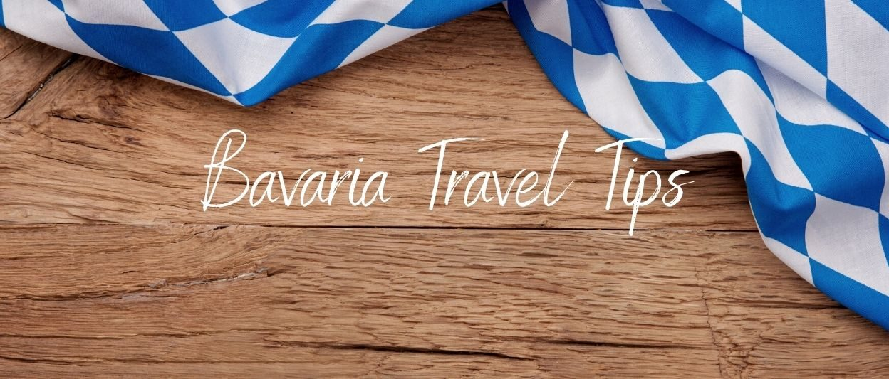 Blue white bavarian flag on a wood table. white text overlay: Bavarian Travel Tips