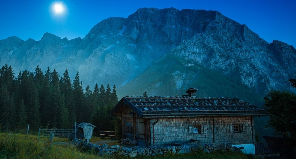An old farm barn on a meadow in the Bavarian alpes near Berchtesgaden Bavaria at night with the moon shining on the night sky