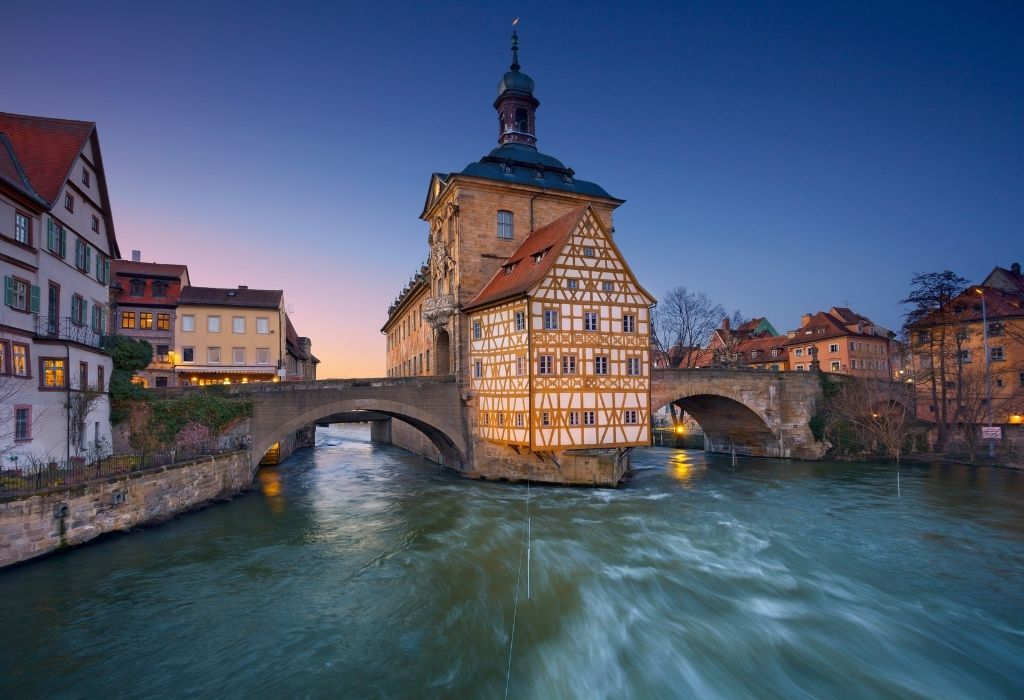 two arched bridges over a river with a yellow/white half-timbered house in the middle of the bridge - City Hall Bamberg