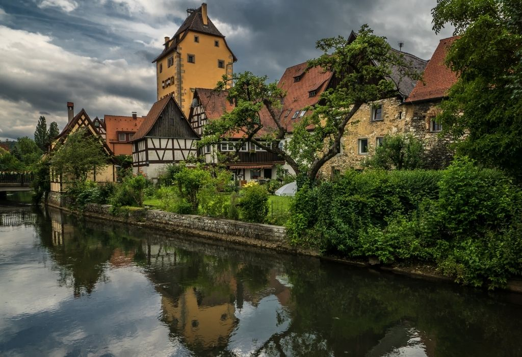 small half-timbered houses and a tall orange tower along a river in Hersbruck, Bavaria