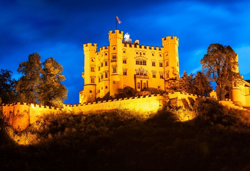 Hohenschwangau Castle lid up with lights, shining orange during blue hour