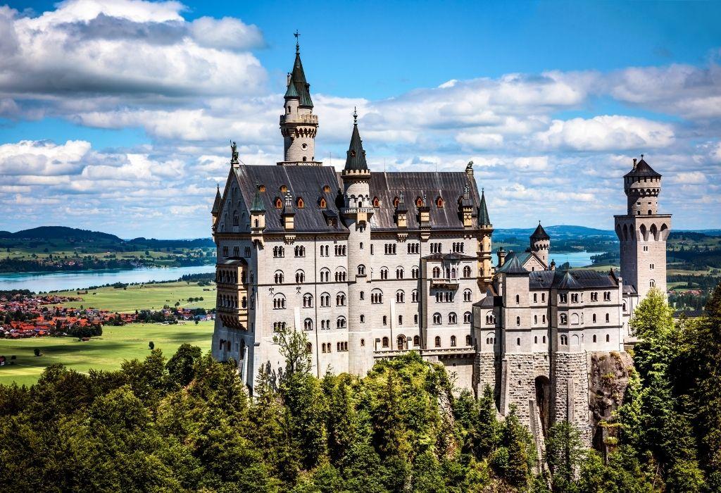 Neuschwanstein Castle - a large white fairytale castle on top of a wooded hill near Füssen