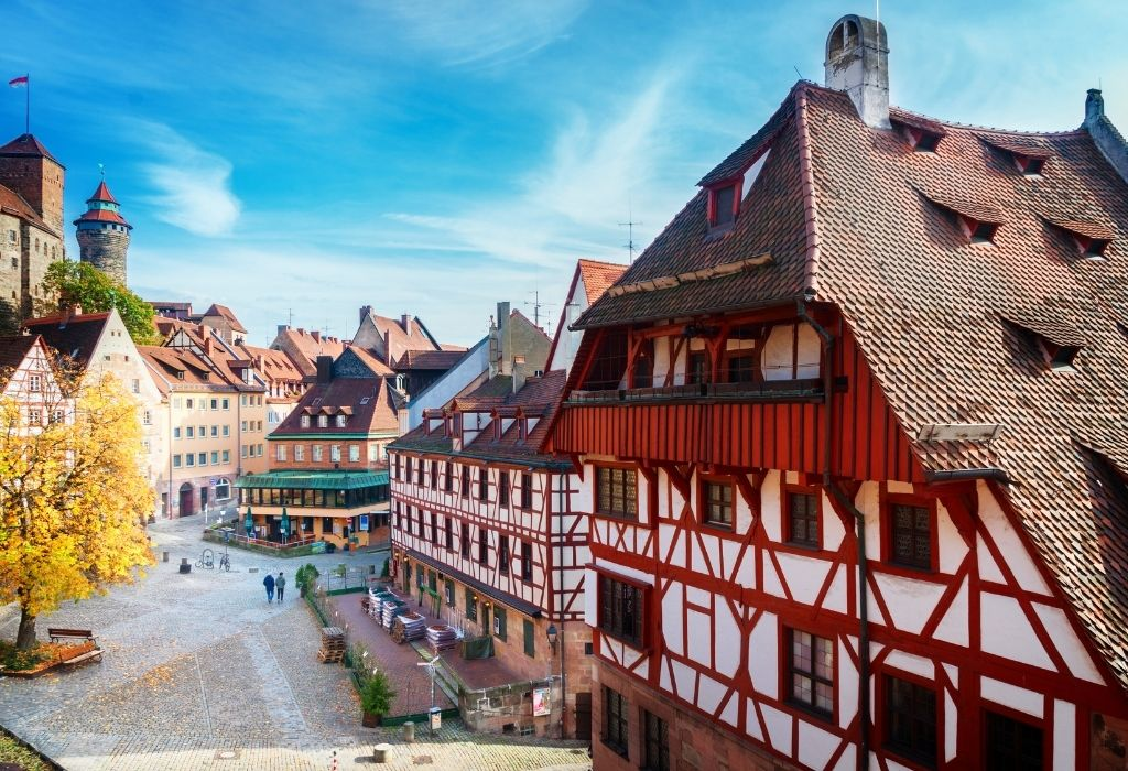 Halftimbered medieval houses with red wood and white walls on the right, a small city square in the center and a stone tower to the left