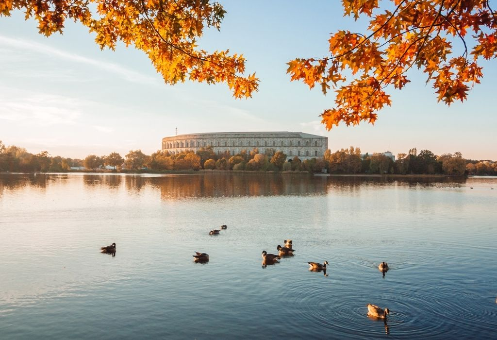 A lake with ducks and fall foilage in the foreground and the round former NAZI rally grounds (now a museum) in the background