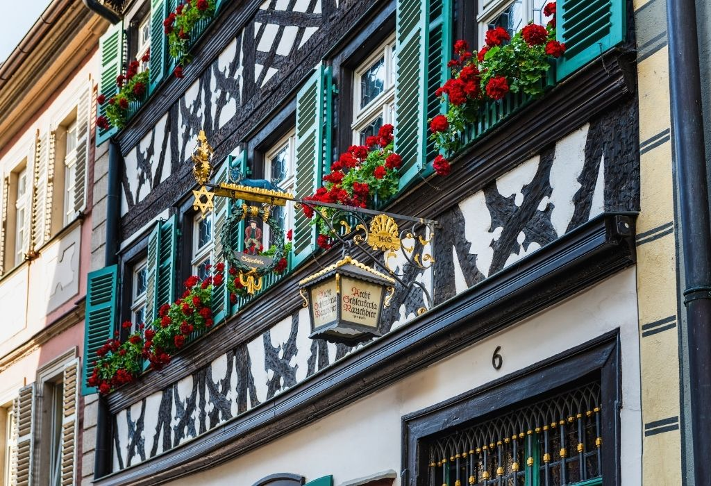 Half timbered house with black wood and white walls and green window shutters - Brewery Schlenkerle Bamberg