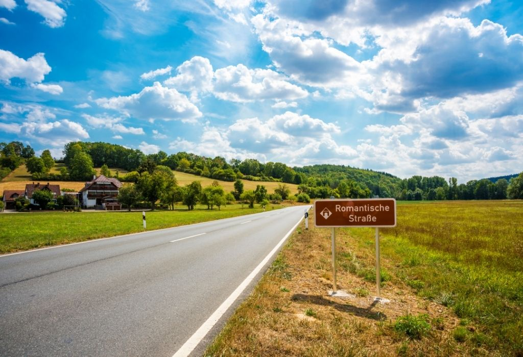"""Small country road in Bavaria through a field and a small group of houses  with a brown sign on the right """"Romanic Road"""""""