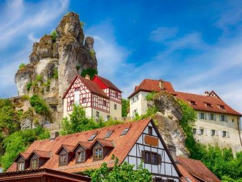 Halftimbered houses with red tiled roofs perched on a steep mountain with a large rock formation towering over the village - Tuchersfeld Bavaria