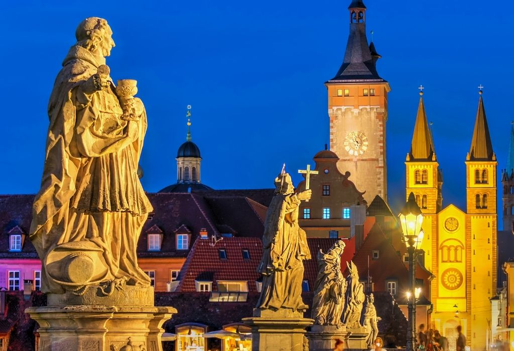 Stone statues of saints on a bridge in Würzburg, Bavaria, with the old city and cathedral in the background